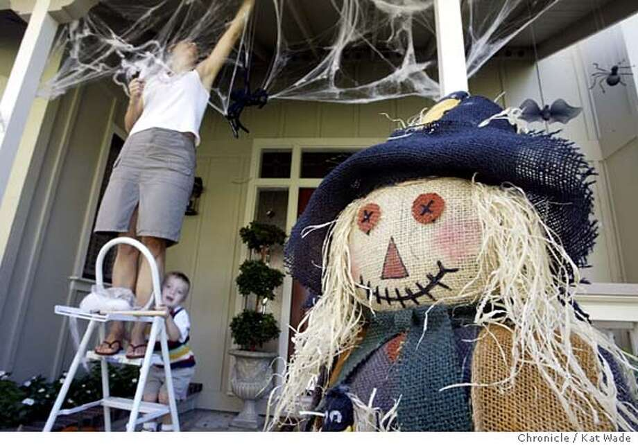 Mary Ann Corbett and her youngest son Daniel, 2, hang Halloween decorations on the porch of their Danville home on 10/27/03. Kat Wade / The Chronicle Photo: Kat Wade
