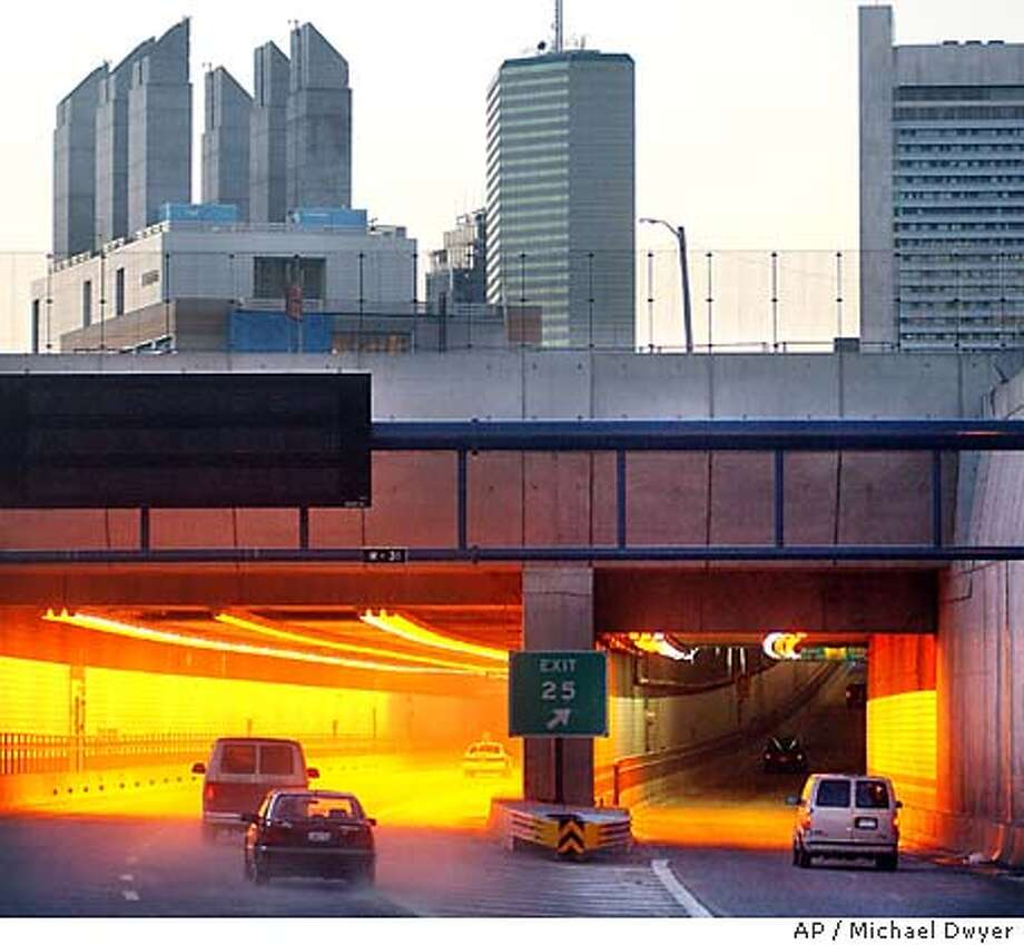 "Vehicles, left, enter a portion of the "" "" Central Artery Project tunnel which connects the Massachusetts Turnpike with Logan International Airport, moments after the section was opened to general traffic for the first time, Saturday, Jan. 18, 2003, in Boston. The $6.5 billion, 1.3-mile tunnel allows people to drive from Logan to Washington state without getting off Interstate 90. (AP Photo/Michael Dwyer) Photo: MICHAEL DWYER"