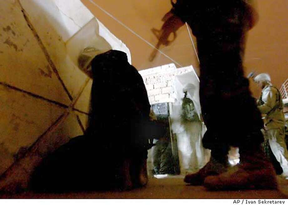 U.S. Army's 4th Infantry Division soldier guards a suspect with a hood on his head during a night raid in Saddam Hussein's home town of Tikrit, 193 km (120 miles) north of Baghdad, Iraq, Thursday, Oct. 30, 2003. U.S. soldier detained 4 men who are belived to be involved in terrorist cells and 10 others for questioning. (AP Photo/Ivan Sekretarev) Photo: IVAN SEKRETAREV