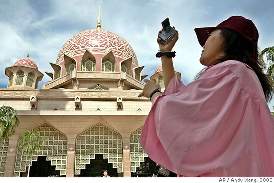 TRAVEL **FOR IMMEDIATE RELEASE** A tourist films the Putrajaya Mosque constructed in rose-tinted granite with a soaring 380-feet-tall minaret on the banks of an artificial lake in Putrajaya, Nov. 19, 2003. (AP Photo/Andy Wong) Photo: ANDY WONG