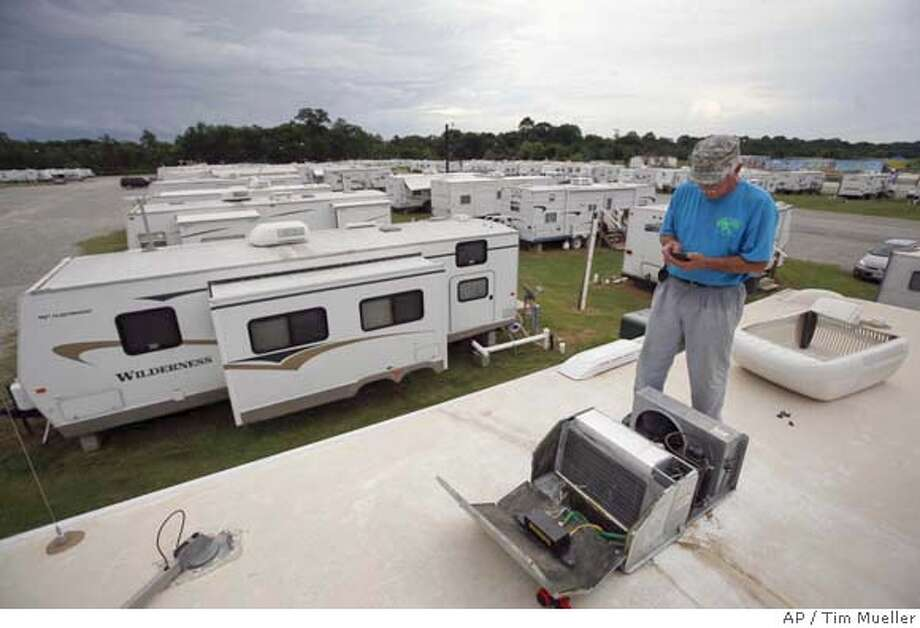 Don Kehoe of LEC Maintenance makes a call from the top of a FEMA trailer at Renaissance Village, Friday, July 20, 2007, in Baker, La. Kehoe was checking the air conditioning unit on the trailer. (AP Photo/Tim Mueller) Photo: Tim Mueller