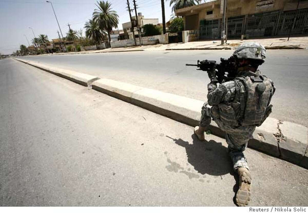 A U.S. soldier looks through his rifle's scope at a street in Yarmuk neighbourhood during a patrol in Baghdad July 20, 2007. REUTERS/Nikola Solic (IRAQ) Ran on: 07-21-2007 A U.S. soldier looks through his rifles scope at a street in Yarmuk neighborhood in Baghdad.