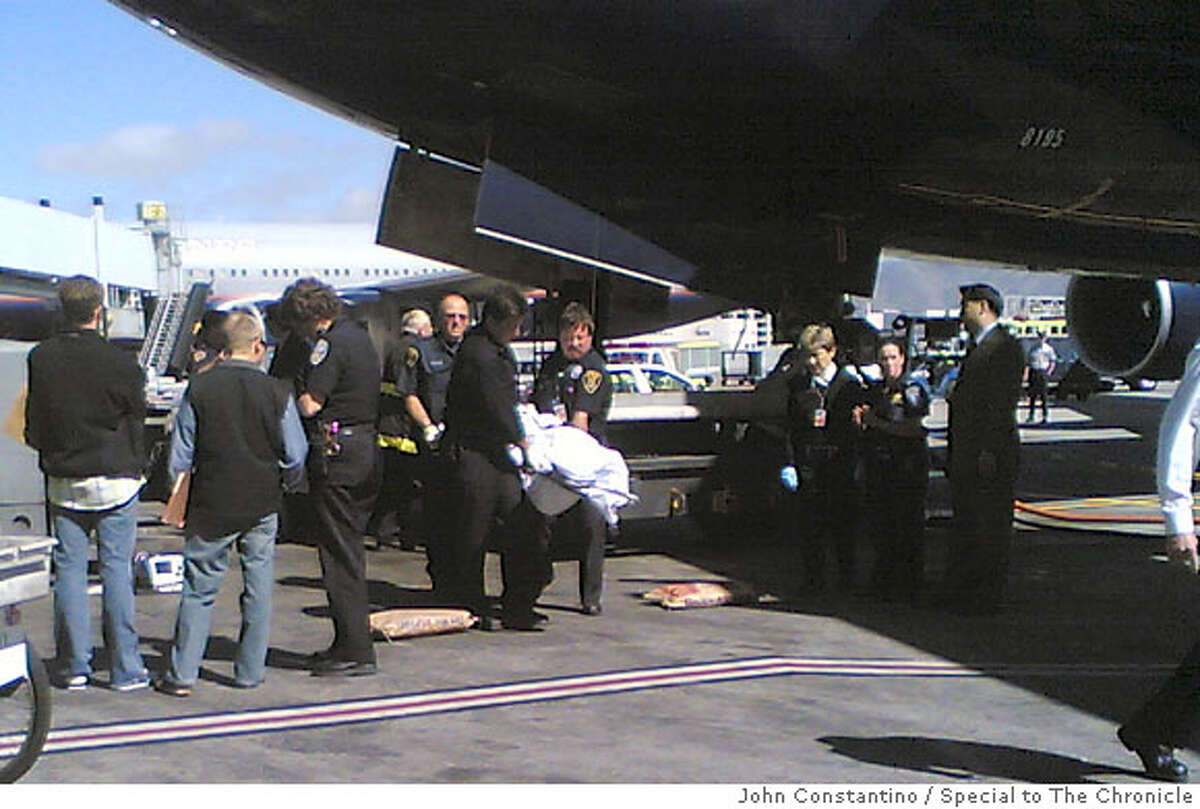 An unidentified body is removed from United Airlines flight 858 from Shanghai at San Francisco Airport Thursday, July 19, 2007. John Constantino / Special to The Chronicle