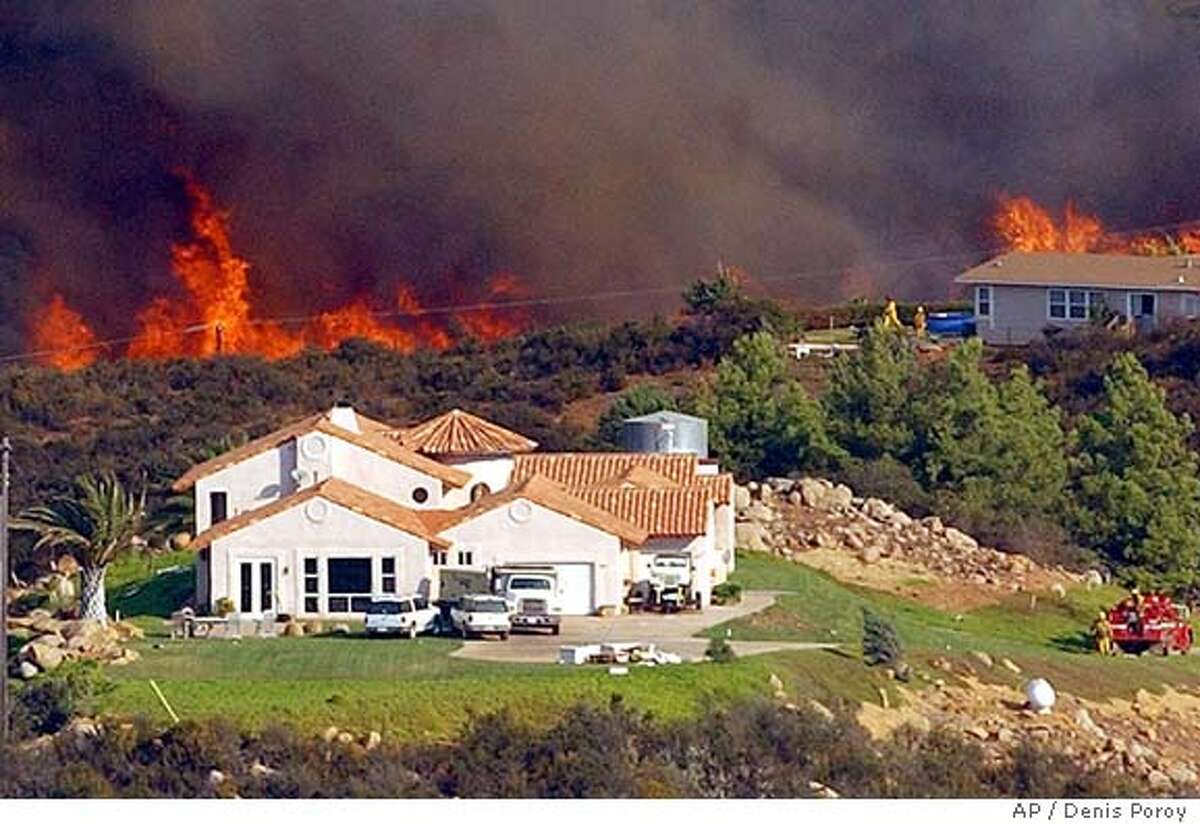 Firefighters work to protect two homes on a remote hillside in Bear Valley, south of Valley Center, Calif., Monday, Oct. 27, 2003. A state of emergency was declared in Los Angeles, San Bernardino, San Diego and Ventura counties as the fires laid to waste entire blocks of homes, closed major highways and roads, shuttered some schools, disrupted air travel nationwide, and literally sent people running for their lives. (AP Photo/Denis Poroy)