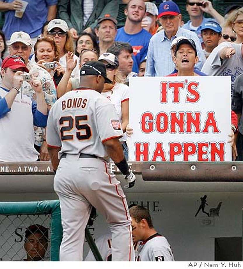 San Francisco Giants' Barry Bonds steps into the dugout as fans take photographs and hold up a sign during the first inning of a baseball game against the Chicago Cubs Thursday, July 19, 2007 in Chicago. Bonds hit his 752nd career home run in the second inning, three shy of equaling Hank Aaron's record. (AP Photo/Nam Y. Huh) Photo: Nam Y. Huh