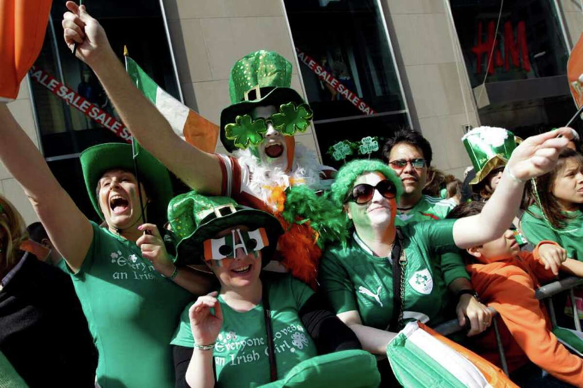 Deirdre Kelly, left, Linda Forth, second from left, Darren McCarthy, center, and Eimear Ni Bhriain, of Dublin, Ireland, cheer on the marchers during the 251st annual St. Patrick's Day Parade, Saturday, March 17, 2012 in New York.