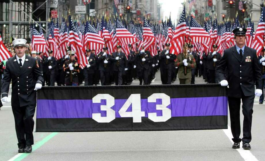 Firefighters carrying 343 American flags representing the firefighters that died during the terrorist attacks on the World Trade Center march up 5th Ave. during the 251st annual St. Patrick's Day Parade,  Saturday, March 17, 2012 in New York. Photo: Mary Altaffer, AP / AP