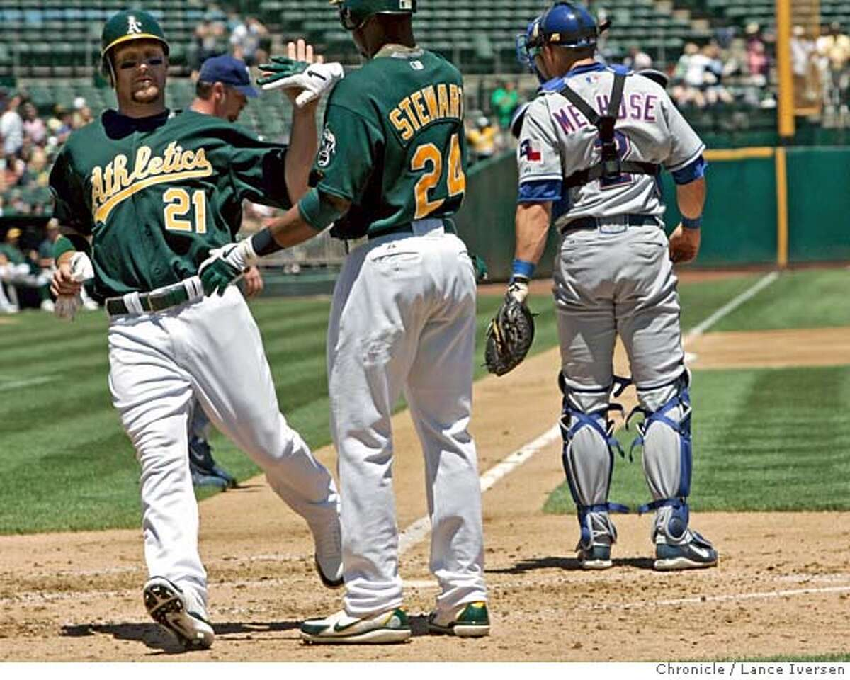 ATHLETICS_50158.JPG A's #21 Mark Kotsay is greeted by Shannon Stewart as he crosses home plate to score another A's run in the 2nd inning. The Oakland Athletics defeated the Texas Rangers at McAfee Coliseum in Oakland 6-0(July18) Lance Iversen/The Chronicle (cq) SUBJECT 7/18/07,in OAKLAND. CA.