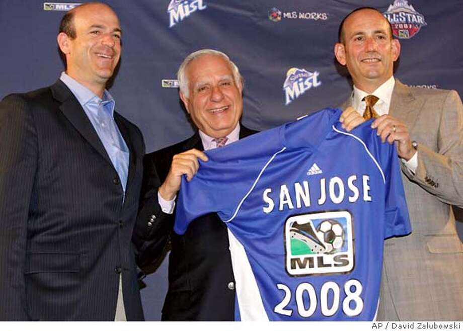 Don Garber, right, commissioner of Major League Soccer, joins the new owners of the San Jose Earthquakes, Lew Wolff, center, and John fisher, left, in holding up a jersey for the expansion team during a news conference in the northeast Denver suburb of Commerce City, Colo., on Wednesday, July 18, 2007. Garber announced that the league will give a franchise to San Jose for the 2008 season and plans are in the works for two more expansion franchises by 2010. (AP Photo/David Zalubowski) Photo: David Zalubowski