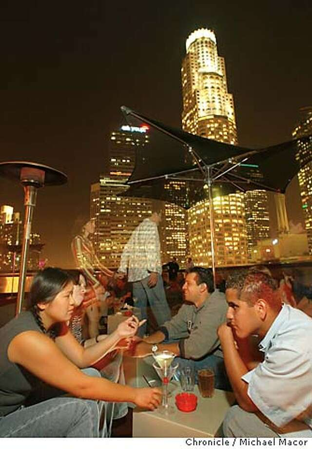 "The ""Standard Hotel"" along S. Flower St. Lily Chow, Erica Morales, Jesse James and Robert smith enjoy drinks atop the ""Rooftop"" bar. The open air ""Rooftop"" bar against the downtown skyline.With the near opening of the Disney Concert Hall, a look at the club scene of the surrounding area. The changing face of the club culture of the downton Los Angeles area.  10/17/03 in LOS ANGELES. MICHAEL MACOR/ The Chronicle Photo: MICHAEL MACOR"