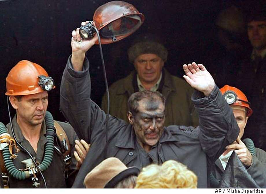 A miner waves after he was brought to the surface by rescue workers at the Zapadnaya mine in Novoshakhtinsk, southern Russia, Saturday, Oct. 25, 2003. Rescue workers on Saturday began lifting to the surface 46 miners trapped underground in a flooded mine shaft for nearly two days in southern Russia. (AP Photo/Misha Japaridze) Photo: MISHA JAPARIDZE