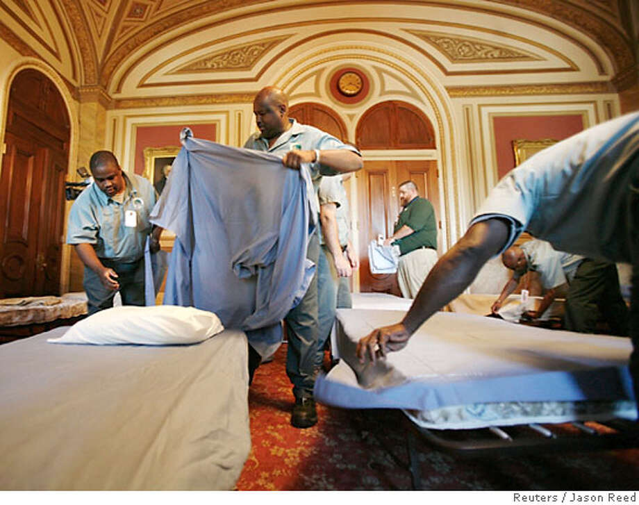Workers lay out cots for U.S. Senators in the Lyndon B. Johnson room, just off the Senate floor, in the U.S. Capitol Building in Washington July 17, 2007. U.S. Senate Democrats, hoping to raise pressure on President George W. Bush and his fellow Republicans to pull troops from Iraq, have scheduled an around-the-clock war debate starting on Tuesday which is expected to last overnight. REUTERS/Jason Reed (UNITED STATES) Photo: JASON REED