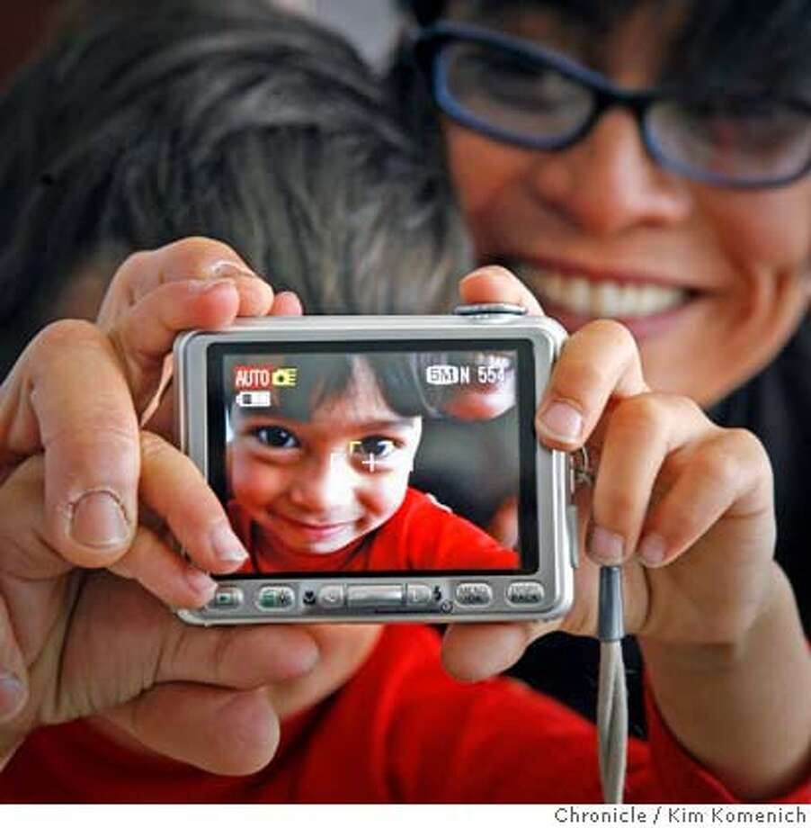 DIGITAL16_011_KK.JPG  Sebastien Bachar (cq both), age 4, takes uses his digital camera as his mother J.D. Beltran holds him. Beltran is a multi-media artist, photographer and SF Art Institute professor. She is one of the people quoted in a Guthmann piece about the impact of digital photography on the personal lives of casual users and on the professional lives of fine-art and commercial photographers.  Photo by Kim Komenich/The Chronicle  J.D. Beltran, Sebastien Bachar MANDATORY CREDIT FOR PHOTOG AND SAN FRANCISCO CHRONICLE. NO SALES- MAGS OUT. Photo: Kim Komenich