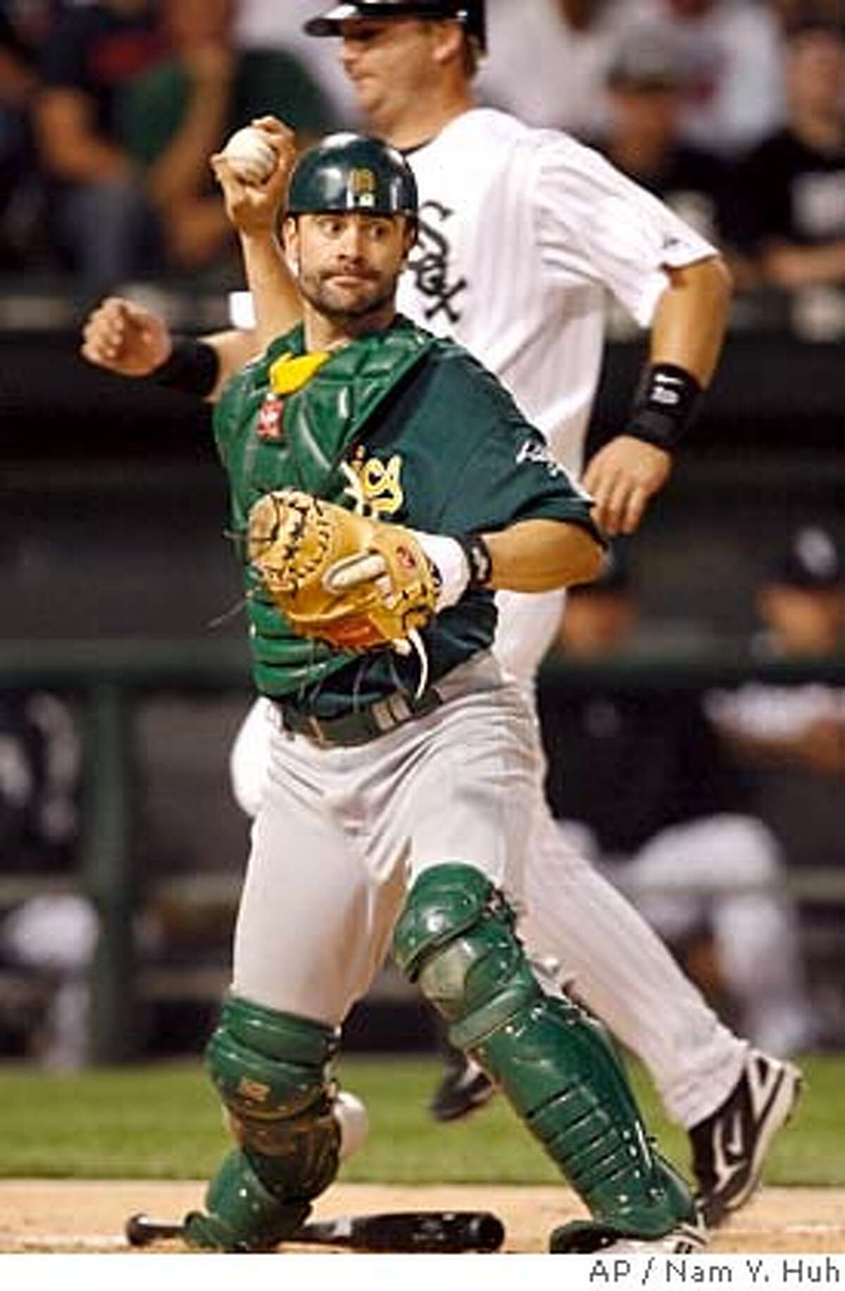 ** FILE ** Oakland Athletics catcher Jason Kendall, front, looks to throw to first after forcing out Chicago White Sox's A.J. Pierzynski at home plate in this file photo from a baseball game, Wednesday, May 23, 2007, in Chicago. Kendall is back in the National League after being acquired by the Chicago Cubs Monday, July 16, 2007. The Oakland Athletics sent the veteran catcher and cash to the Cubs for receiver Rob Bowen and minor league pitcher Jerry Blevins. (AP Photo/Nam Y. Huh)