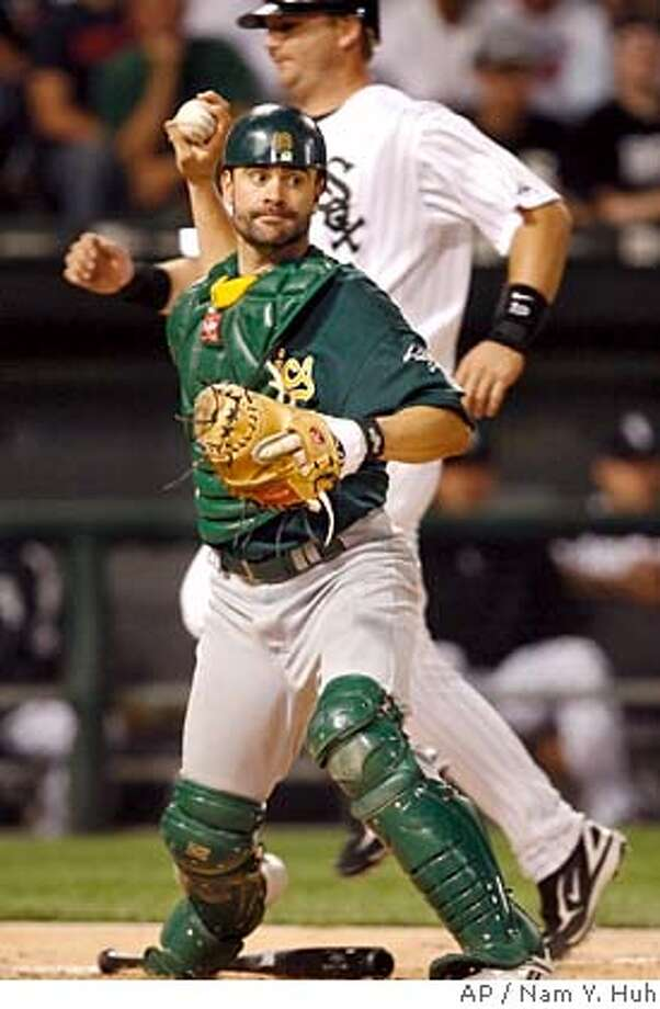 ** FILE ** Oakland Athletics catcher Jason Kendall, front, looks to throw to first after forcing out Chicago White Sox's A.J. Pierzynski at home plate in this file photo from a baseball game, Wednesday, May 23, 2007, in Chicago. Kendall is back in the National League after being acquired by the Chicago Cubs Monday, July 16, 2007. The Oakland Athletics sent the veteran catcher and cash to the Cubs for receiver Rob Bowen and minor league pitcher Jerry Blevins. (AP Photo/Nam Y. Huh) Photo: Nam Y. Huh
