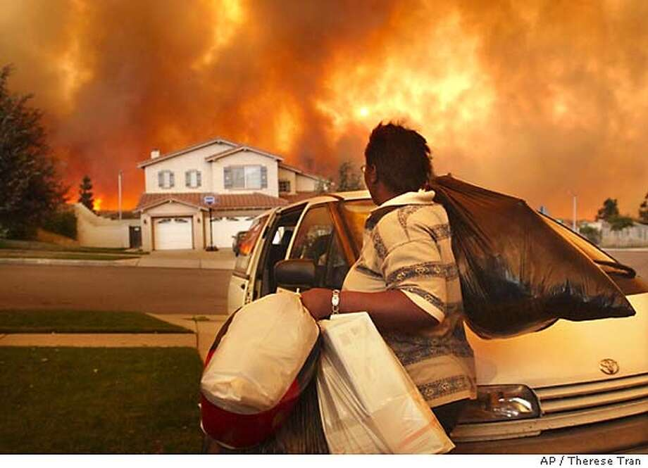 A Rancho Cucamonga resident gathers belongings to evacuate as flames move closer to her north Rancho Cucamonga, Calif. neighborhood, early Friday morning, Oct. 24, 2003. (AP Photos/Inland Valley Daily Bulletin, Therese Tran) ** MANDATORY CREDIT * Photo: THERESE TRAN