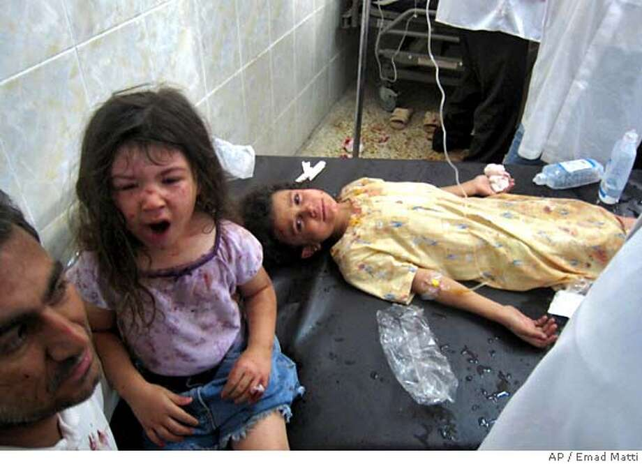An Iraqi girl lies wounded after twin suicide car bombings exploded within 20 minutes of each other in Kirkuk, 290 kilometers (180 miles) north of Baghdad, Iraq, on Monday, July 16, 2007, killing at least 80 people and wounding around 150 in attacks targeting a Kurdish political office and ripping through an outdoor market, police said. The attacks began around noon when a suicide bomber detonated his explosives-packed truck near the concrete blast walls of the headquarters of the Patriotic Union of Kurdistan, the party of Iraqi President Jalal Talabani.Soon after, the second bomber attacked the Haseer market, 700 meters (yards) away, destroying stalls and cars, said Kirkuk police Brig. Sarhat Qadir. (AP Photo/Emad Matti) Photo: EMAD MATTI