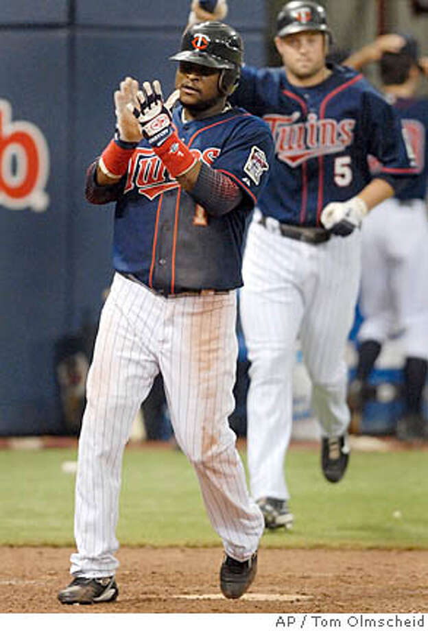 Minnesota Twins' Luis Castillo, front, who tripled, celebrates while scoring the winning run after teammate Joe Mauer singled in the ninth inning against the Oakland Athletics in a baseball game, Sunday, July 15, 2007 in Minneapolis. Michael Cuddyer (5) runs out to join the celebration. Minnesota won 4-3.(AP Photo/Tom Olmscheid) Photo: Tom Olmscheid