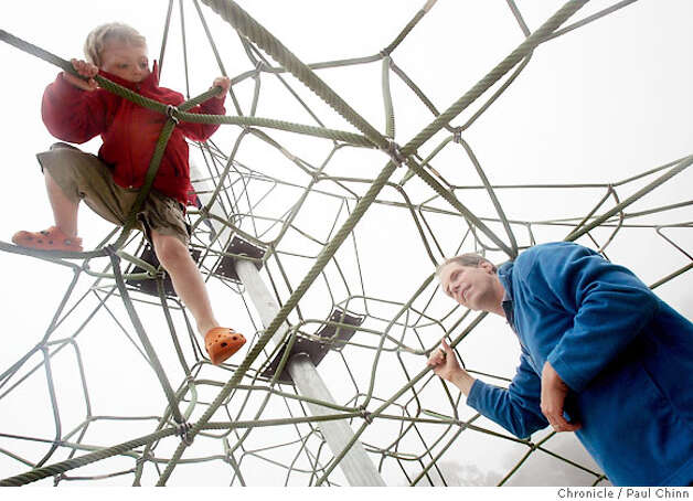 Four-year-old Shea Smith climbs down from a rope structure with his dad Greg watching when the Children's Playground reopened at Golden Gate Park in San Francisco, Calif. on Saturday, July 14, 2007. The $3.8 million renovation project on the playground, that originally opened in 1887, took a year-and-a-half to complete.  PAUL CHINN/The Chronicle  **Shea Smith, Greg Smith Photo: PAUL CHINN