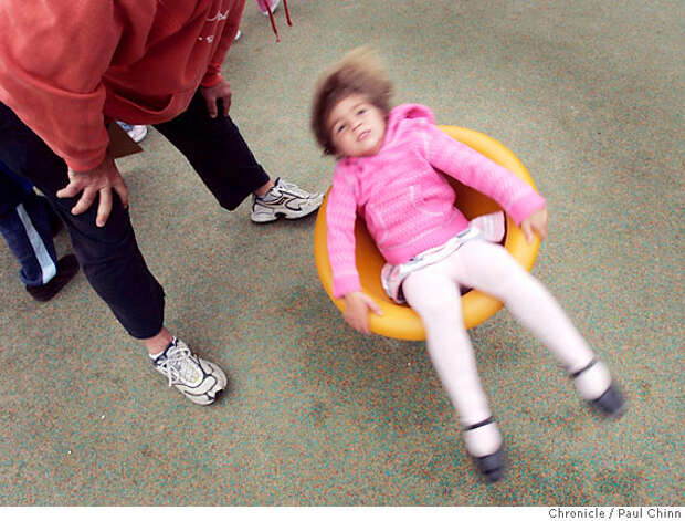 Molly Lindsey, 4, takes a spin on a crooked seat, with help from her dad John (left) at the Children's Playground in Golden Gate Park in San Francisco, Calif. on Saturday, July 14, 2007. The $3.8 million renovation project on the playground, that originally opened in 1887, took a year-and-a-half to complete.  PAUL CHINN/The Chronicle  **Molly Lindsey, John Lindsey Photo: PAUL CHINN