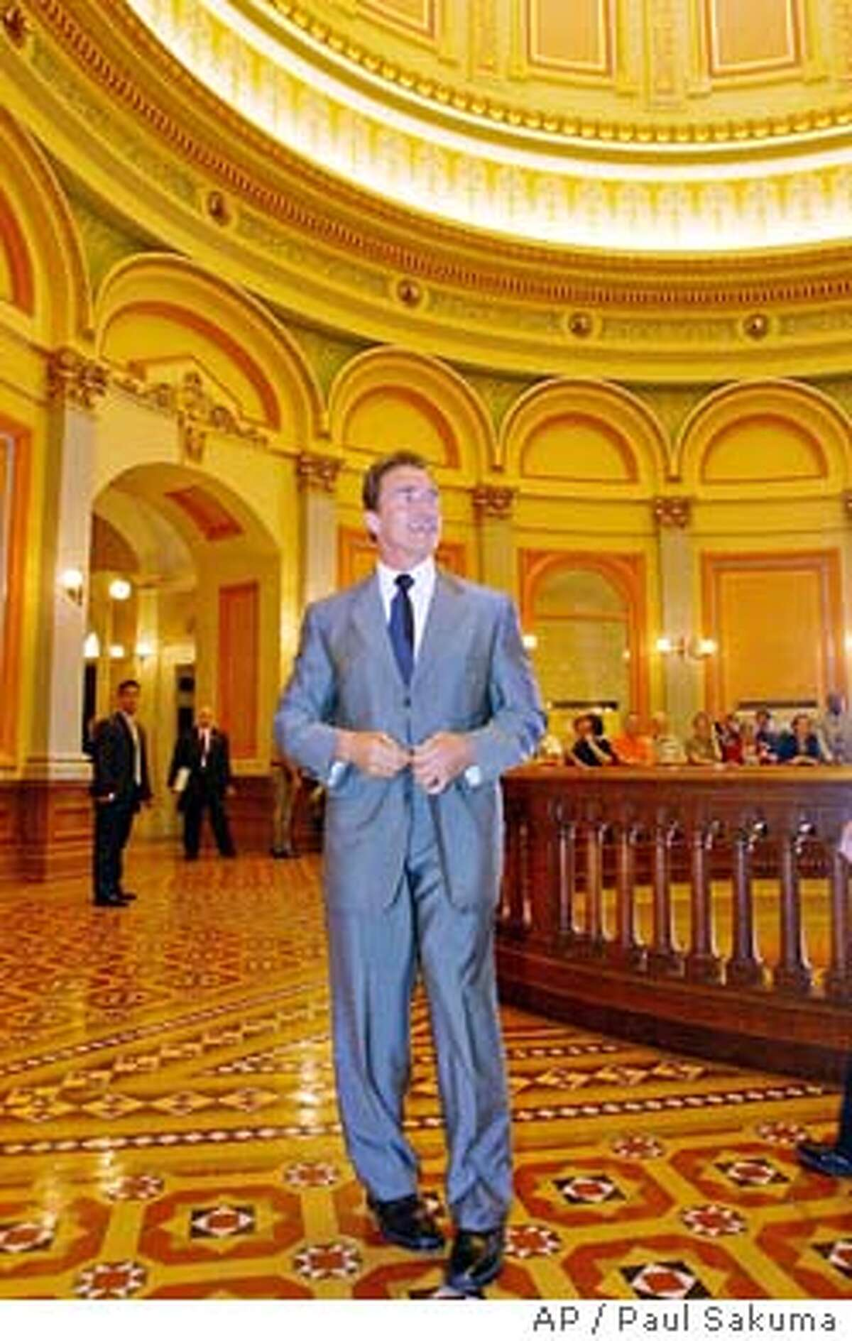 Gov.-elect Arnold Schwarzenegger walks through the rotunda of the state Capitol during a visit to legislators in Sacramento, Calif., Wednesday, Oct. 22, 2003. Schwarzenegger used his first official visit to the state Capitol Wednesday to name a health care executive and former aide to Republican former Gov. Pete Wilson as his new chief of staff. (AP Photo/Paul Sakuma)