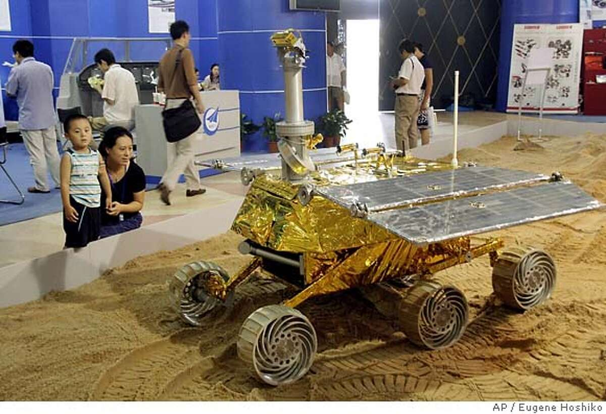 Visitors watch a Chinese-made moon explorer machine displayed at International Aerospace Technology and Equipment Exhibition Thursday July 5, 2007 in Shanghai, China. China put two astronauts into orbit for a week in 2005 and officials have said they want to put a man on the moon and build a space station in the next 10 or 15 years. (AP Photo/Eugene Hoshiko)
