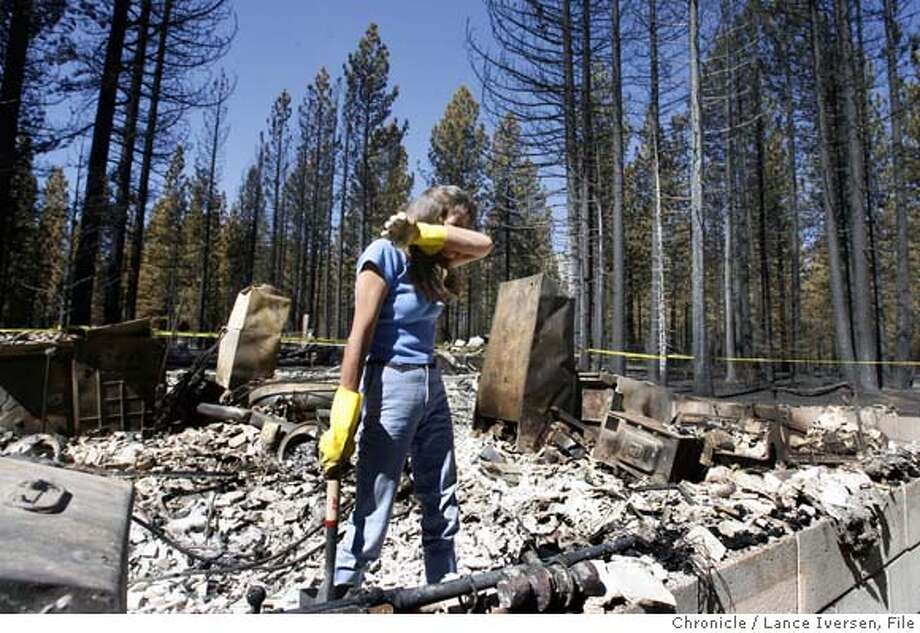 TAHOEFIRE_45038.JPG  Cheryle Pinnkney returned to her parent�s home on Zuni St in Meyers to help her father Edward Schlinger look for family treasures lost in Sunday night�s firestorm. Homeowners were allowed to return to their Meyers property for the first time Thursday since Sunday's mandatory evacuation. South Lake Tahoe's Angora Fire continues to burn, but at a much slower pace. To date the fire has consumed 229 homes in Meyers and South Lake Tahoe. An additional 3,000 acres of forest have been lost or damaged.(June 28) (cq) SUBJECT) Lance Iversen / The Chronicle Photo taken on 6/28/07,in MEYERS, CA. Ran on: 07-15-2007  Cheryle Pinnkney searches last month through her father's home destroyed by the Angora Fire. Photo: By Lance Iversen