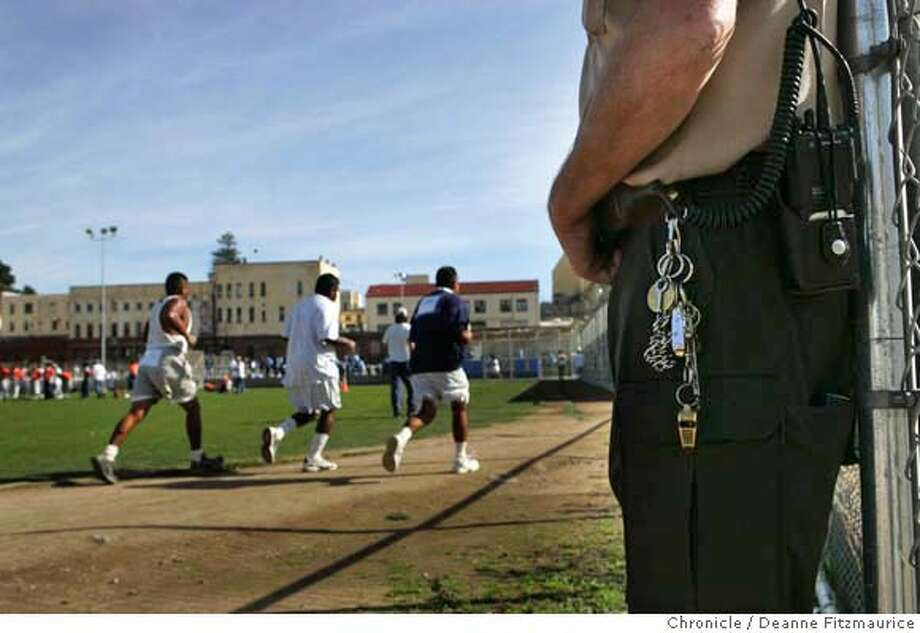 sanquentin_206_df.JPG  A guard stands watch as inmates from San Quentin 1,000 Mile Running Club run for two hours to raise money for Children's Hospital Oakland. Deanne Fitzmaurice / San Francisco Chronicle Photo: Deanne Fitzmaurice