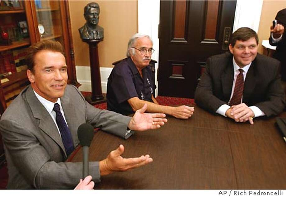 Gov.-elect Arnold Schwarzenegger, left, answers a reporter's question while meeting with legislative leaders at the Capitol in Sacramento, Calif., Wednesday, Oct. 22, 2003. Schwarzenegger met with members of the legislative leadership, including State Sen. John Burton, D-San Francisco, center, and Sen. Minority Leader Jim Brulte, R-Rancho Cucamonga. (AP Photo/Rich Pedroncelli) Photo: RICH PEDRONCELLI