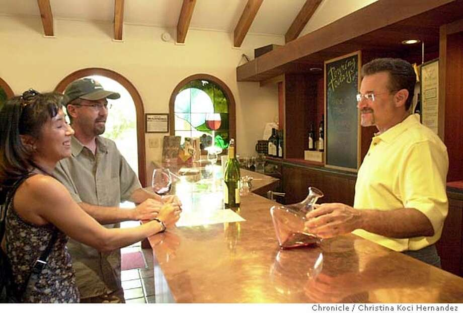 {092503_tastingroom/cuvaison_kocihernandez}  Sales employee, mark Scheinholz demonstrates a rolling glass decantor, invented for use on ships. Guests not interested in giving names.Cuvaison winery, tasting room. Shot on9/25/03 in Calistoga.  CHRISTINA KOCI HERNANDEZ / The Chronicle Photo: CHRISTINA KOCI HERNANDEZ