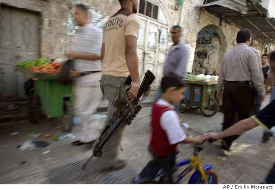 "A Palestinian militant from the Al Aqsa Martyrs Brigades, a group linked to the Fatah Movement, holds his weapon as he walks along the central market at the Old City in the West Bank city of Nablus Saturday July 14 2007. Israel also was considering a deal to remove dozens of Fatah militants from its wanted list, in exchange for guarantees they would suspend operations against Israel, the Palestinians said. ""There are the beginnings of an agreement,"" said Kamel Ghanam on Saturday, a leader of the Al Aqsa Martyrs' Brigades, a violent offshoot of Abbas' Fatah movement. Ghanam said the militants could sign an agreement with Israel, and ""if they sign, Israel will stop chasing them."" Talks are continuing on who is eligible for amnesty, he said. (AP Photo/Emilio Morenatti) Photo: EMILIO MORENATTI"