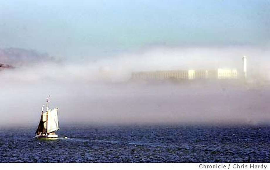 Fog coming in through the Golden Gate lightly covering Alcatraz with a sail boat going past  Event on 10/21/03 in San Francisco. CHRIS HARDY / The Chronicle MANDATORY CREDIT FOR PHOTOG AND SF CHRONICLE/ -MAGS OUT Magazine#Metro#Chronicle#10/22/2003#ALL#5star##0421450284 Photo: CHRIS HARDY