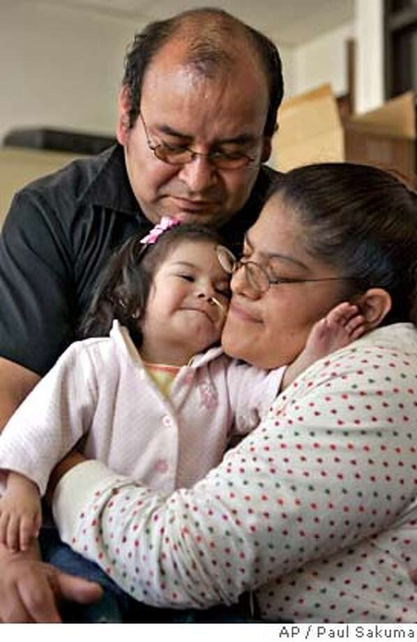 Victor and Maria Roa hug their daughter, Hazelle, in San Francisco, Monday, July 9, 2007. Hazelle Roa has a little-known genetic disorder that is likely to require specialized medical care in the United States, but her parents are illegal immigrants from Mexico who have been ordered out of the country by immigration officials. (AP Photo/Paul Sakuma) Photo: Paul Sakuma
