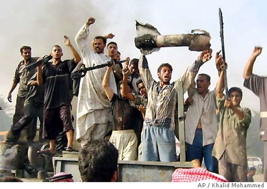 Iraqi's celebrate with a burned out rocket while cheering and dancing atop a burned out U.S. Army military ammunition truck after it was attacked in Fallujah, Iraq, Sunday, Oct. 19, 2003, 35 miles (60 kms) west of Baghdad. (AP Photo/Khalid Mohammed) Photo: KHALID MOHAMMED
