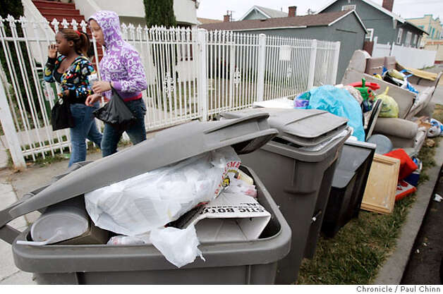 Two women walk past garbage and debris on Birch Street near 98th Avenue in Oakland, Calif. on Wednesday, July 11, 2007. A labor dispute between Waste Management Inc., who locked-out employees, is into its second week.  PAUL CHINN/The Chronicle Photo: PAUL CHINN