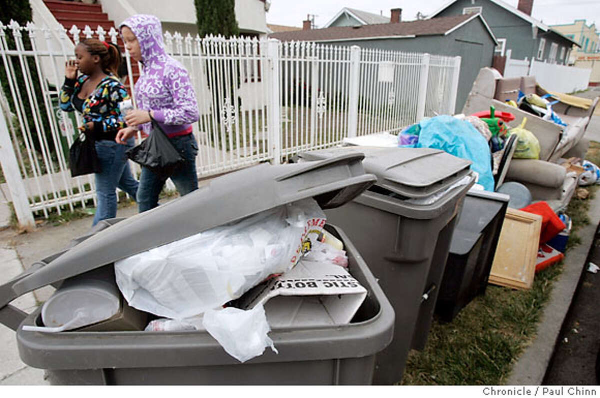 Two women walk past garbage and debris on Birch Street near 98th Avenue in Oakland, Calif. on Wednesday, July 11, 2007. A labor dispute between Waste Management Inc., who locked-out employees, is into its second week. PAUL CHINN/The Chronicle