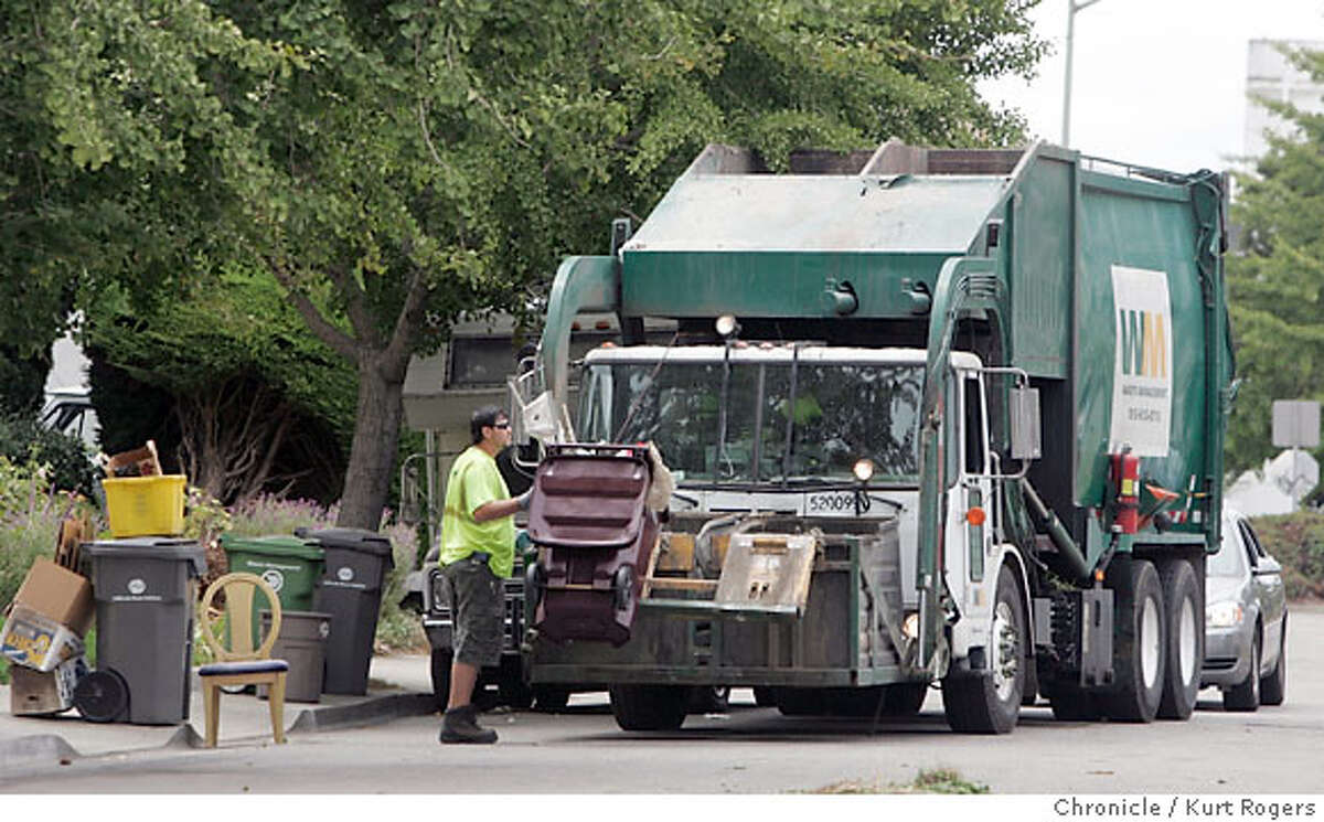 The Garbage is piling up in Oakland as a Garbage collector picks up trash from Magnolia St at 16 St the car behind the truck with Nevada license plates fallowed the truck around on every pickup. WEDNESDAY, JULY 11, 2007 KURT ROGERS OAKLAND SFC THE CHRONICLE