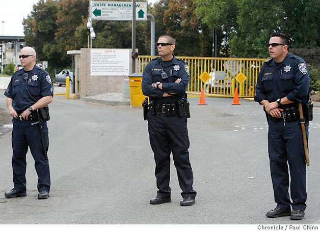 San Leandro police officers guard the entrance to the Waste Management Inc. transfer station during a Teamsters rally to support locked-out sanitation workers in San Leandro, Calif. on Wednesday, July 11, 2007.  PAUL CHINN/The Chronicle Photo: PAUL CHINN