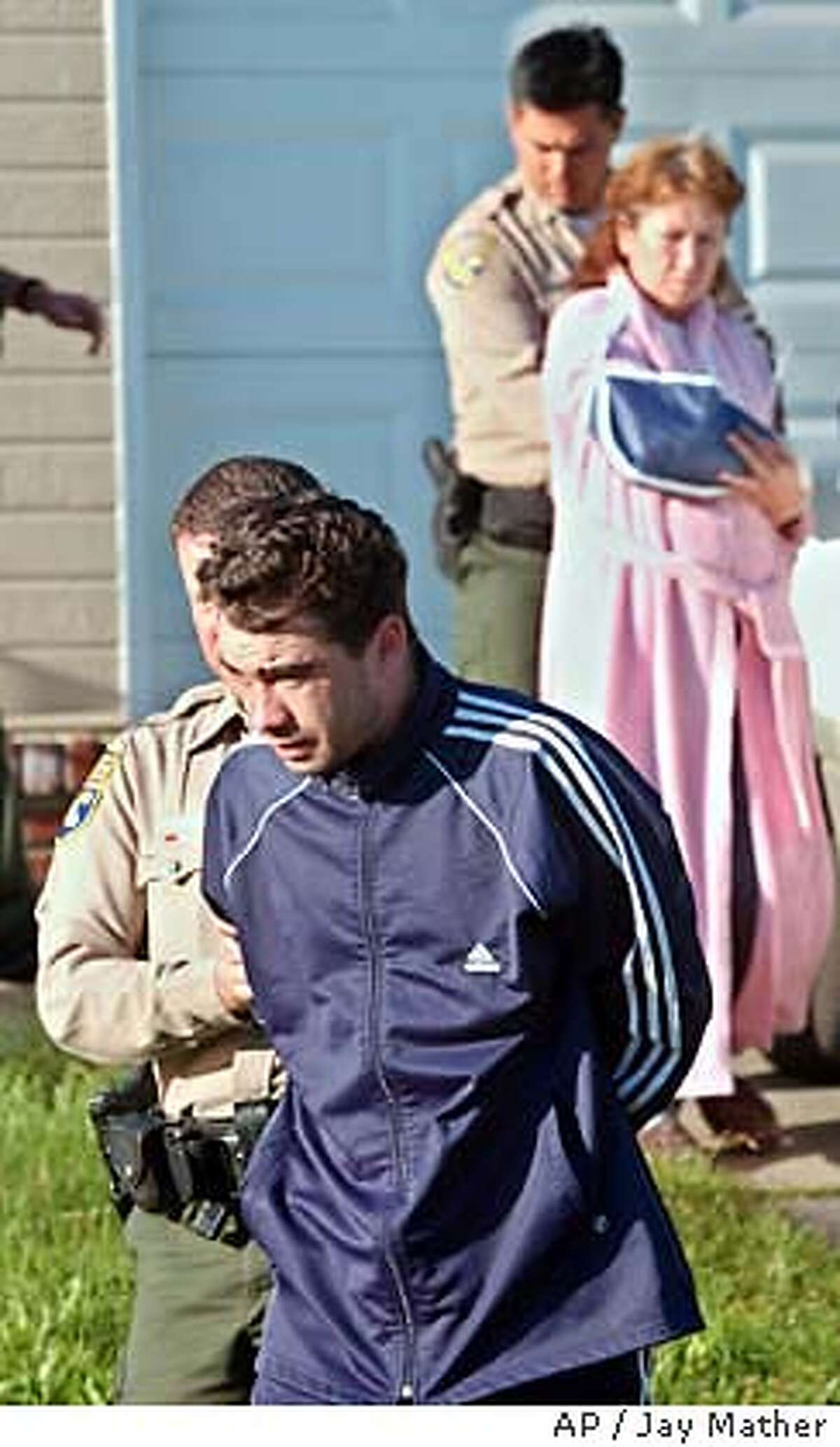 Yuriy Stanislavovich Bugriyev, 27, foreround-right, and Tamara Andreyevna Bugriyev, 51, background-right, wearing bathrobe, are taken into custody by California Department of Fish & Game wardens, Friday, May 9, 2003, in Fair Oaks, Calif. Federal and state wildlife officers broke up an alleged caviar poaching ring Friday, making 10 arrests, including that of the mother and son team shown here, as part of a three-state crackdown on illegal taking of giant white sturgeon from the Sacramento River. (AP Photo/Sacramento Bee, Jay Mather)