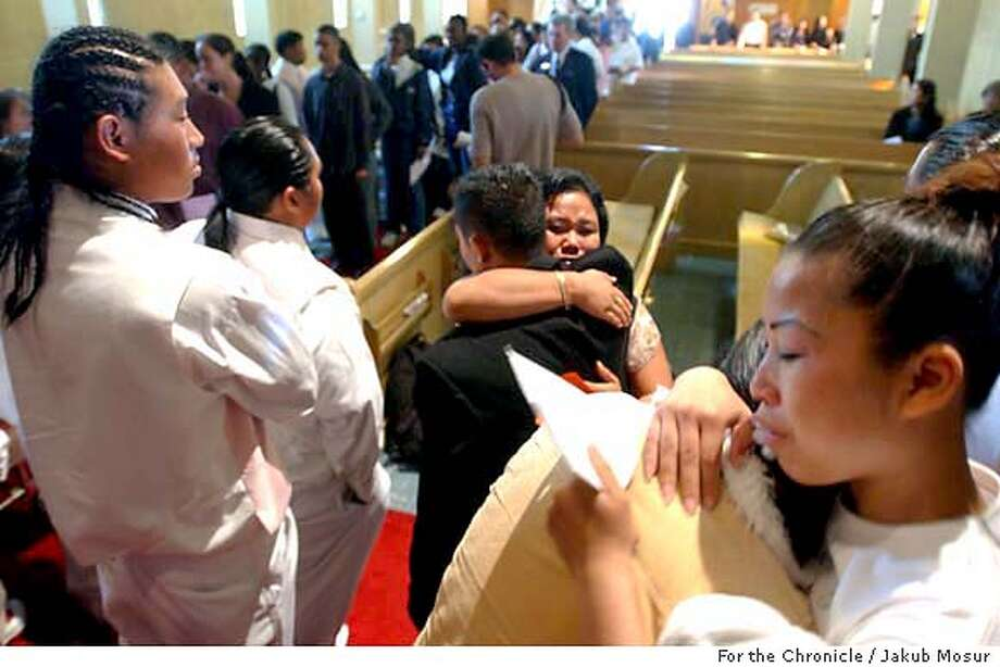 Family members and other mourners hug during the funeral for Chan Boonkeut, 15, at the Grace Lutheran Church in Richmond on Saturday, Oct. 18, 2003. Chan Boonkeut was shot due to her older brother's involvment in a local gang rivalry. Event on 10/18/03 in Richmond. JAKUB MOSUR / The Chronicle Photo: JAKUB MOSUR