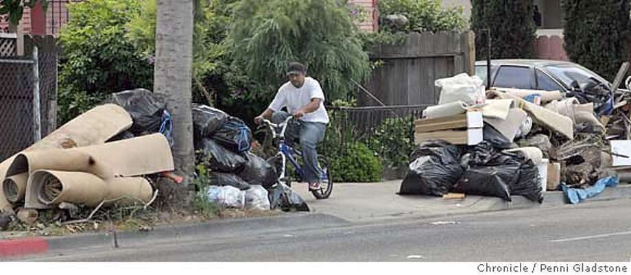 GARBAGE11_PICKUP_020_PG.JPG  A bike rider rides by an accumulation of garbage at C and 98th in Oakland. Resident John Goudeau age 63, was told Monday that his garbage was to be picked up, but by Tues afternoon it hadn't.  Event on 7/10/07 in Oakland.  Penni Gladstone / The Chronicle MANDATORY CREDIT FOR PHOTOG AND SF CHRONICLE/NO SALES-MAGS OUT Photo: Penni Gladstone