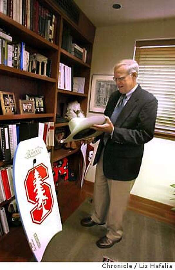 Stanford University president John Hennessy in his office looking at some items given to his university--a hat from Texas and a boogie board from Los Angeles. Shot on 10/15/03 in Palo Alto. LIZ HAFALIA / The Chronicle Photo: LIZ HAFALIA