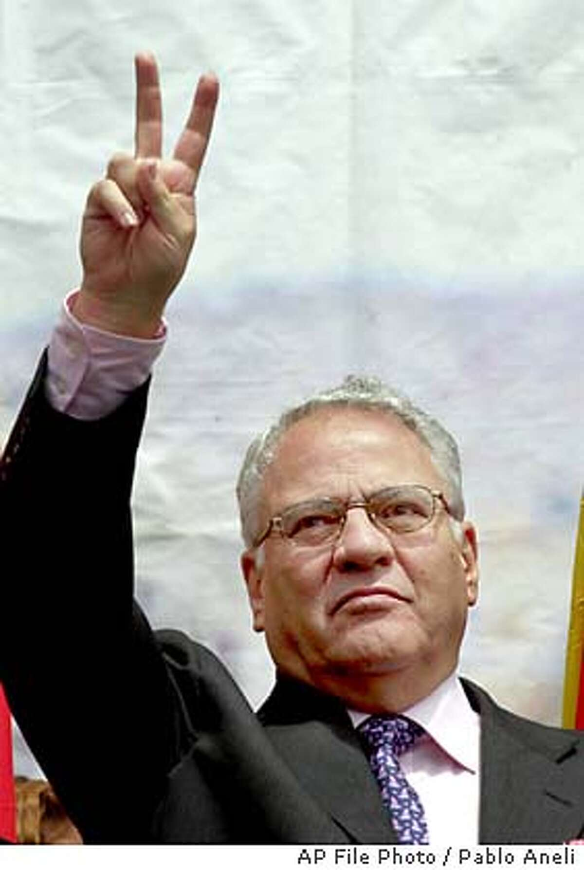 ** FILE ** Bolivian President Gonzalo Sanchez de Lozada, a businessman nicknamed ``Goni'', greets supporters in this April 9, 2002 file photo. The U.S.-educated millionaire who took office for a second term in August 2002 will resign Friday Oct. 17, 2003 after weeks of deadly street riots triggered by a goverment plan to export natural gas, a presidential aide said Friday. (AP Photo/Pablo Aneli, File)