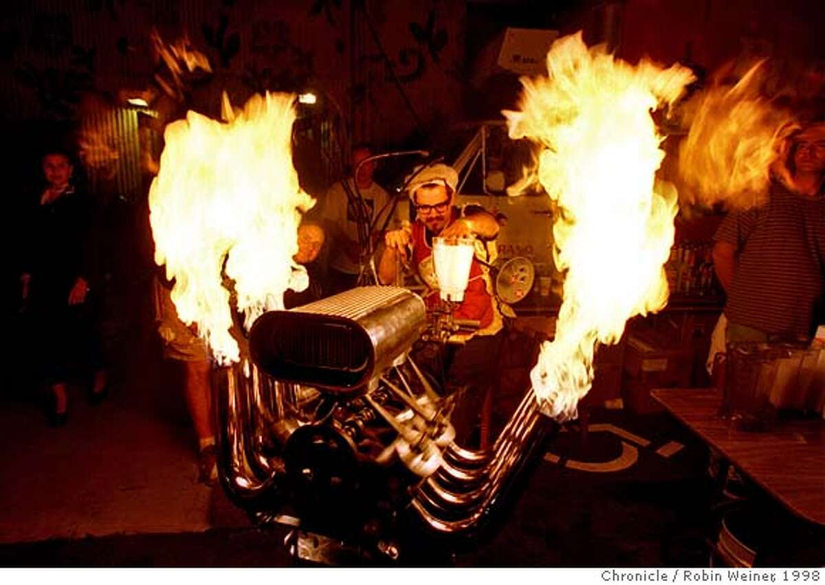 ART CUSTOM/C/1AUG98/DD/RW Artist, Jim Mason, left, the creator of the skeleton V8 engine margarita maker, cranks up the flames while his friend known as Chicken John, center, handles the blender at the Somar Gallery. The party featured hot rod, outsider, graffiti and rock poster artists. PHOTO BY ROBIN WEINER/THE CHRONICLE CAT