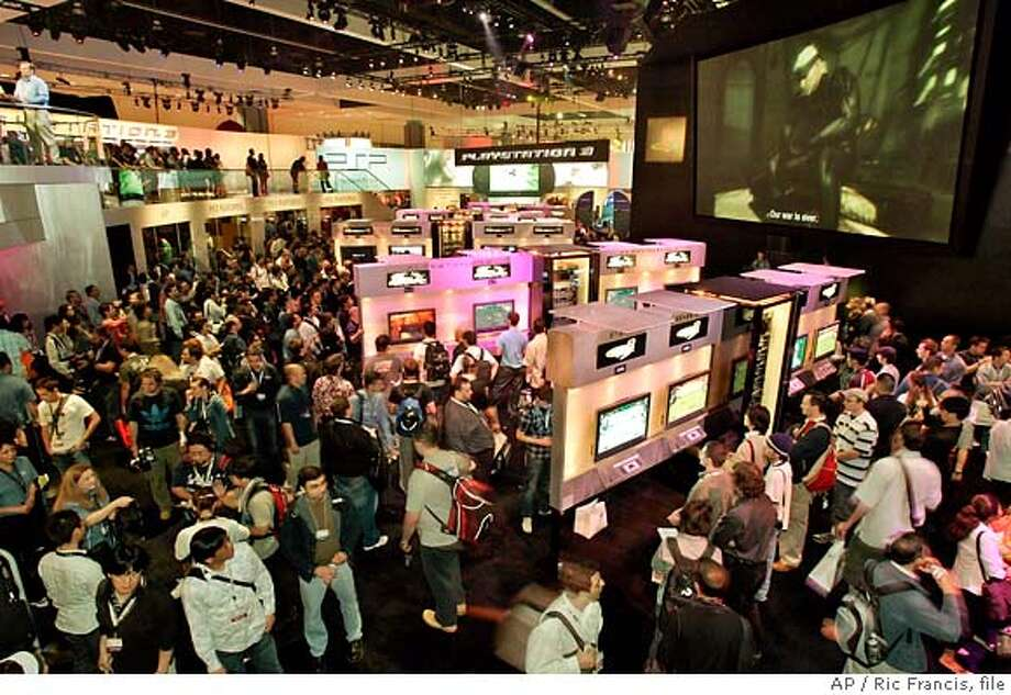 **ADVANCE FOR MONDAY, JULY 9** **FILE** Traders view and play with PlayStation 3 at the Electronic Entertainment Expo in this May 11, 2006 file photo, in the Los Angeles Convention Center. The video game industry's annual showcase is saying goodbye to scantily clad booth babes, extravagant multimillion dollar exhibits, blaring lights and pounding music. There will be no celebrity appearances from the likes of Paris Hilton or Snoop Dogg, either. This year's version of the Electronic Entertainment Expo, renamed the E3 Media & Business Summit, is hoping it can keep the discussion focused on new and upcoming video games. (AP Photo/Ric Francis, file) **ADVANCE FOR MONDAY, JULY 9** MAY 11, 2006 FILE PHOTO Photo: RIC FRANCIS