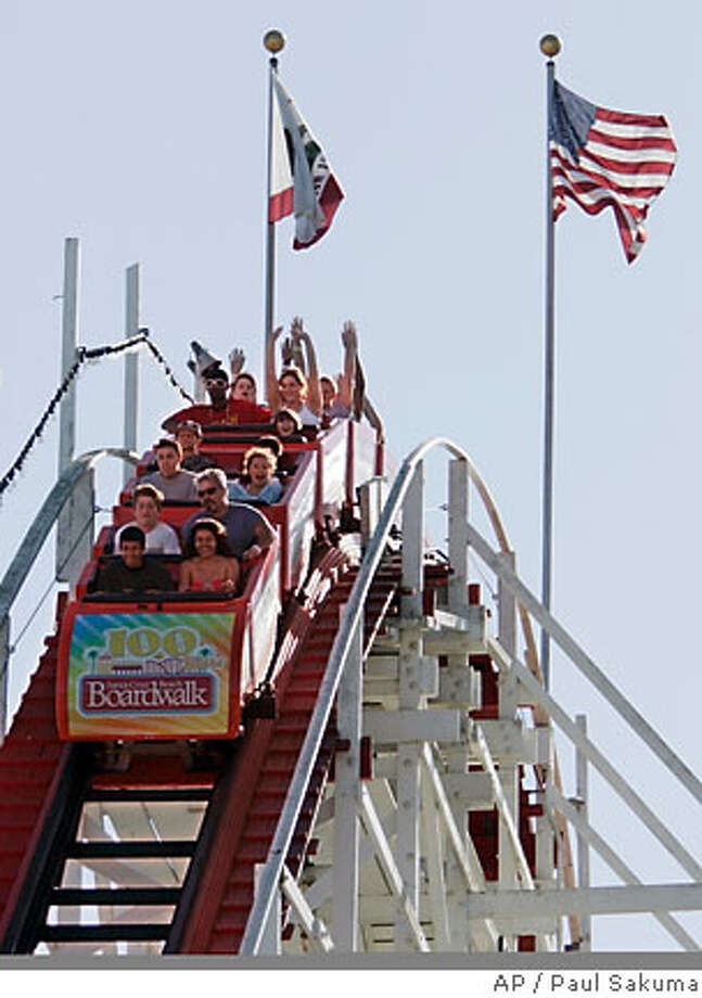 ** FOR IMMEDIATE RELEASE **People ride the Big Dipper at the Santa Cruz Beach Boardwalk in Santa Cruz, Calif., Friday, June 8, 2007. The giant roller coaster, a National Historic Landmark, remains the signature ride at the boardwalk. It began thrilling visitors on May 17, 1924, and its 500 feet of twisting track and wooden construction survived the 1989 Loma Prieta earthquake. (AP Photo/Paul Sakuma) Photo: Paul Sakuma