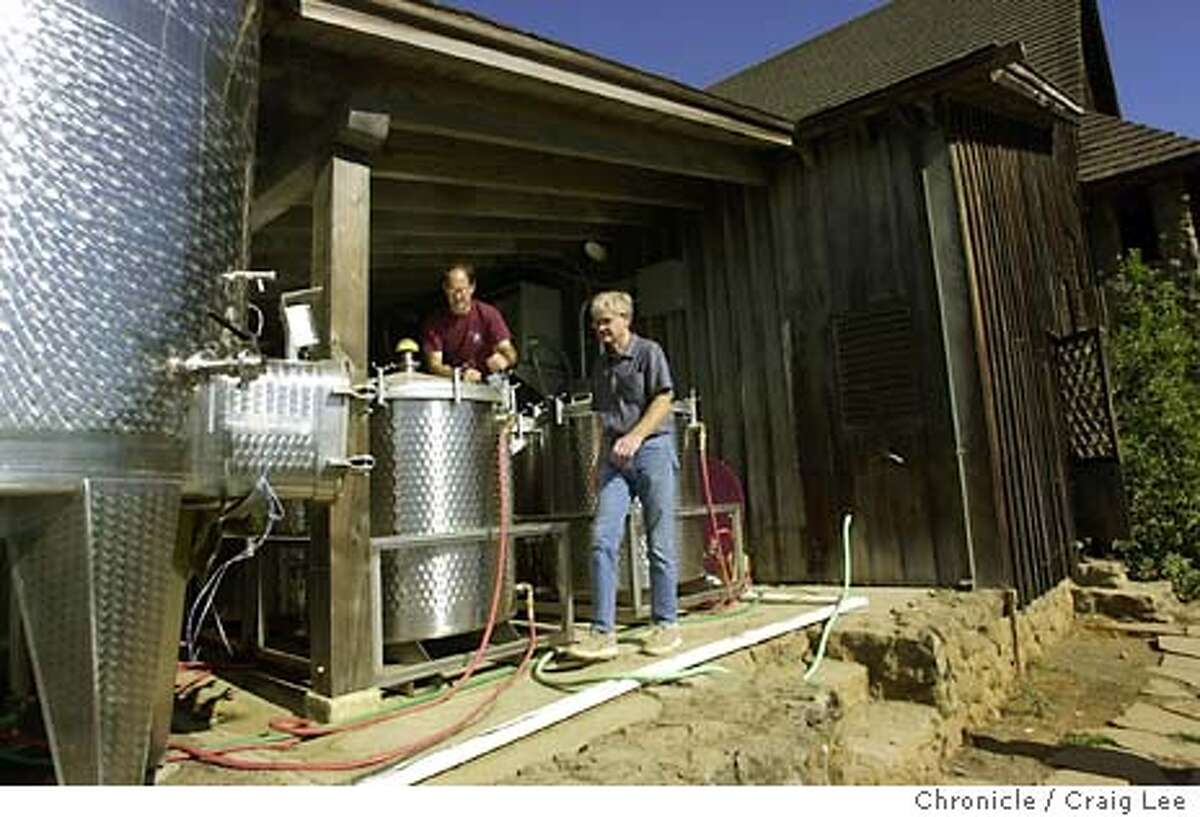 Hanzell Vineyards in Sonoma. Story about the problems of their winery contaminated by TCA, caused when molds come into contact with cleaning agents such as chlorine. They now advise other wineries on how to prevent this disaster. Photo of, Bob Sessions (right), Hanzell's former long-time winemaker who now works as a consultant to the winery and Daniel Docher (left), the present winemaker. This is the temporary outdoor winemaking area while they are constructing a new winery. Event on 10/8/03 in Sonoma. CRAIG LEE / The Chronicle
