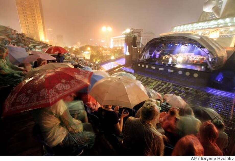 Audience listen performance of English singer Sarah Brightman under thunder storm during the Live Earth concert Saturday, July 7, 2007 at the bottom of Oriental Parl Tower, a landmark of Shanghai, China. Live Earth is staging shows around the world Saturday to draw attention to global warming. (AP Photo/Eugene Hoshiko) Photo: Eugene Hoshiko