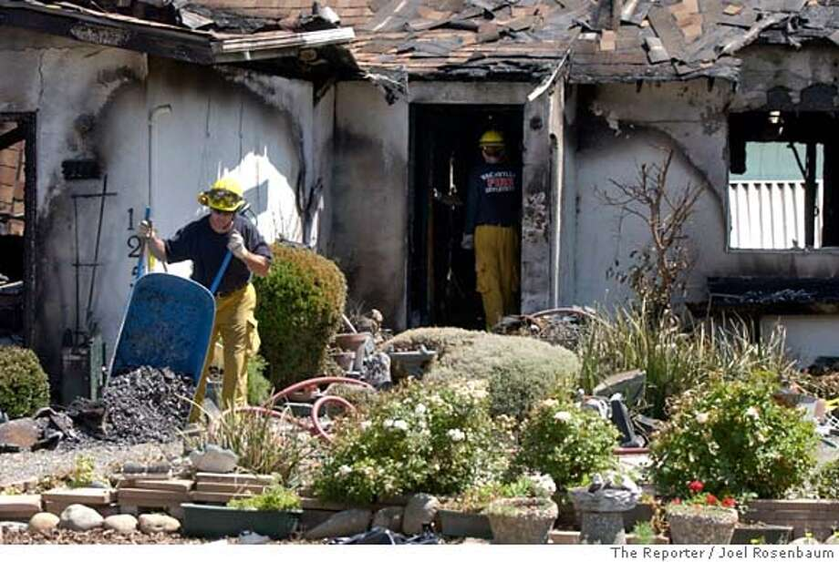 A Vacaville firefighter dumps a pile of ash as an investigation continues into an alleged arson fire at a home Sunday, July 8, 2007, in Vacaville, Calif., where an 88-year old woman was killed Sunday, according to the Reporter newspaper. (AP Photo/The Reporter, Joel Rosenbaum) ** MANDATORY CREDIT, NO SALES ** Photo: Joel Rosenbaum