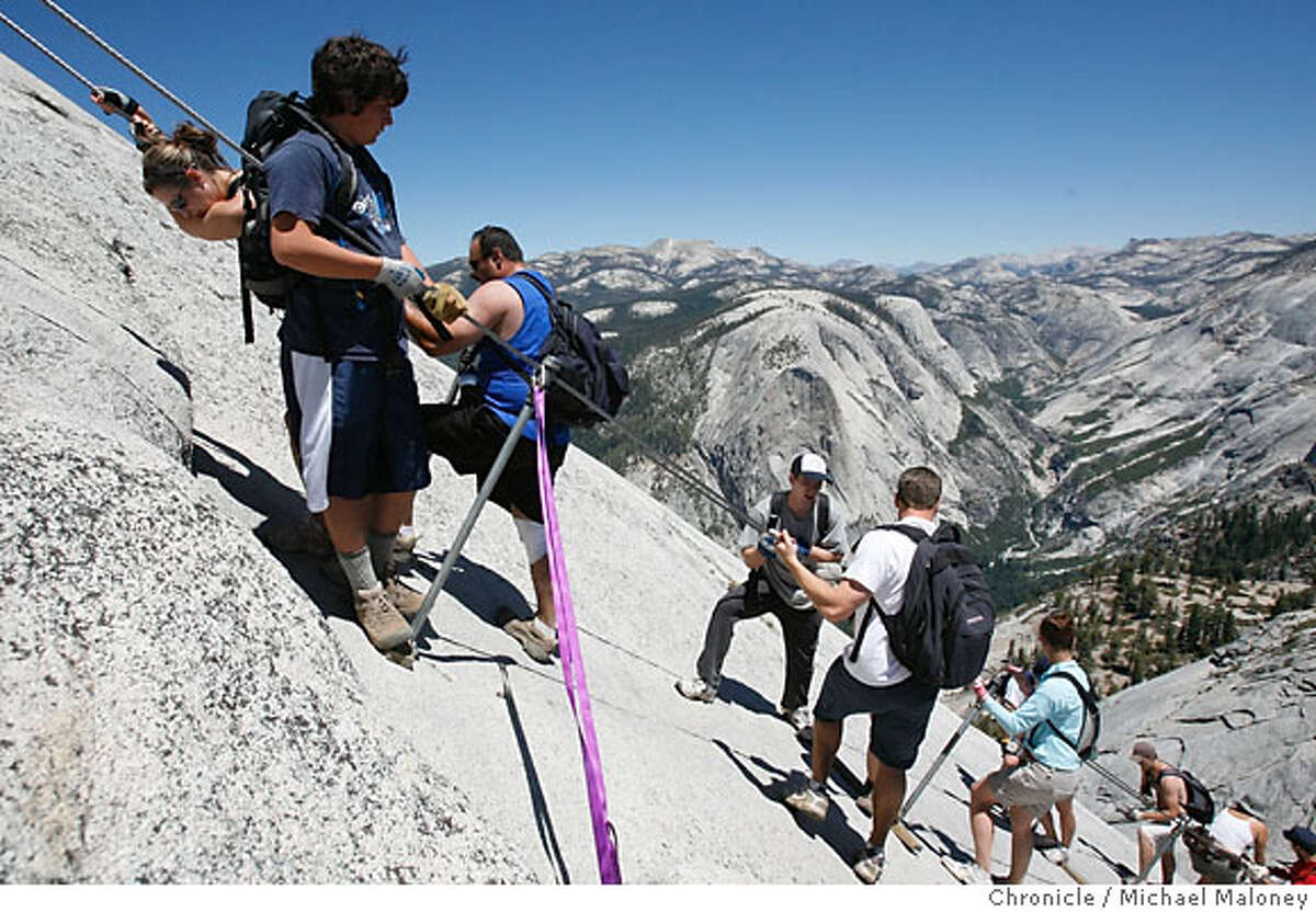 Climbers on the cable section of Half Dome negotiate the steep granite pitch. The weekend summer crowds climbing Half Dome in Yosemite National Park have raised safety concerns among the climbers and park. Hundreds climb the precarious cable section every summer weekend day - many who are not prepared for the strenuous hike and 100 yard cable climb. Photos taken at Half Dome on Saturday, June 30, 2007. Photo by Michael Maloney / San Francisco Chronicle ***